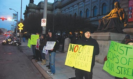 Members of the Pittsburgh Organizing Group are flanked by Pittsburgh Police officers outside of the Dec. 20 inauguration of Mayor Luke Ravenstahl. More than 60 police officers were on hand; only 15 POG members turned out to demonstrate. - CHARLIE DEITCH
