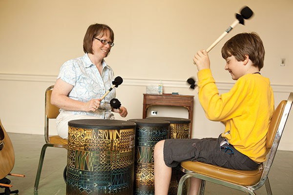 Michelle Montgomery Muth demonstrates a music-therapy drumming exercise, with an assist from the photographer's nephew, Sebastian Mull.