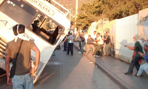 Oaxacans pull a bus on its side to use as a barricade on Oct. 29, the day the federal police entered the city.