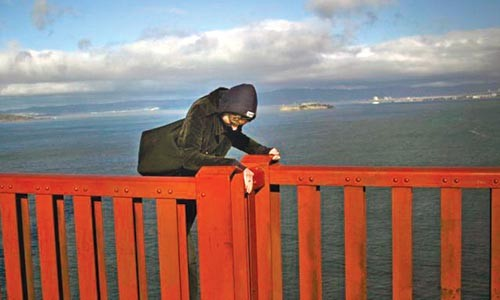 On the edge: As captured by tourist Richard Waters, a would-be jumper scales the railing on the Golden Gate Bridge.