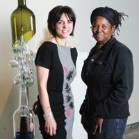 "Pittsburgh Glass Center's Community Relations Coordinator Heather Joy Puskarich and GAGI Festival Director Christine Bethea pose with Melissa Fitzgerald's ""Rainsong Seeks Water."""