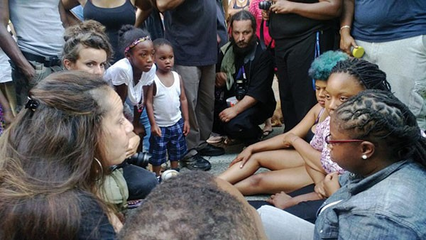 Pittsburgh Police Commander Rashall Brackney, left, talks with residents who sat in the street to protest George Zimmerman's acquittal.