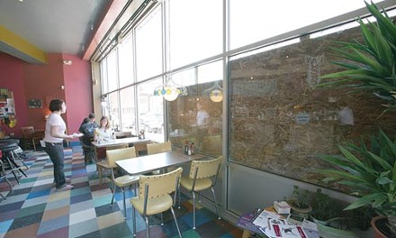 Plywood still covers part of the window damaged by vandals at Garfield's Quiet Storm Coffeehouse. - PHOTO BY HEATHER MULL