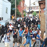 Protesters stream onto Butler Street after pepper-spray canisters are released.