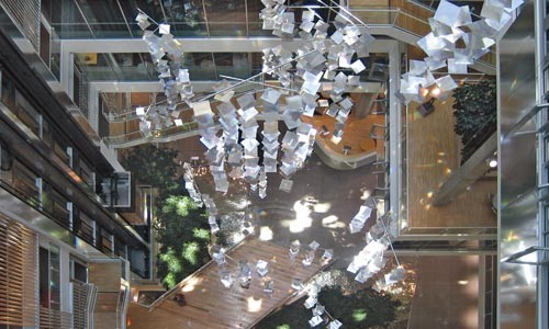 Reflects well: a view from above of the light-dispersing chandeliers in the Genzyme Headquarters, in Boston. Photo courtesy of Behnisch Architekten.