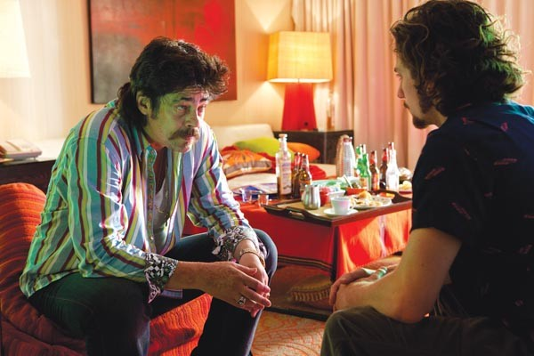 Respect the 'stache, bro: Benicio Del Toro takes a meeting with Aaron Johnson.