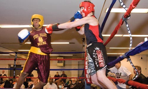 Richard Brooks, left, and Damion Kock exchange blows at the second annual Little Italy Christmas Boxing event in Bloomfield. - BRIAN KALDORF