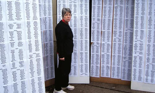Scilla Wahrhaftig, head of the American Friends Service Committee's state office, with a list of the names of American soldiers killed in the Iraq War, being readied for a vigil marking the 3,000th death. - PHOTO BY PAUL WAHRHAFTIG