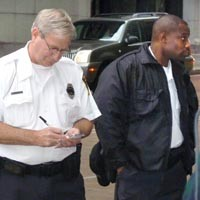 Security guards taking notes at a Sept. 28 protest against government surveillance. - CHRIS POTTER