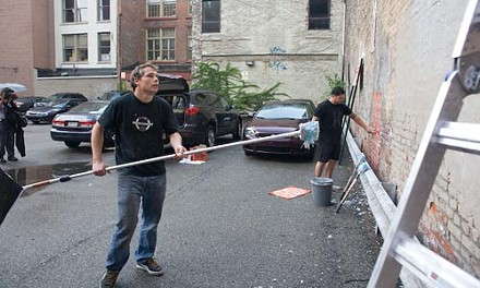 Shepard Fairey (black T-shirt, long-handled brush) and his crew hang a mural on First Street near Wood, Downtown, on Wednesday night. - BILL O'DRISCOLL