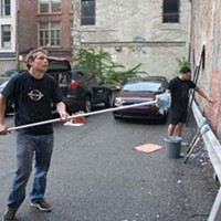 Shepard Fairey (black T-shirt, long-handled brush) and his crew hang a mural on First Street near Wood, Downtown, on Wednesday night.