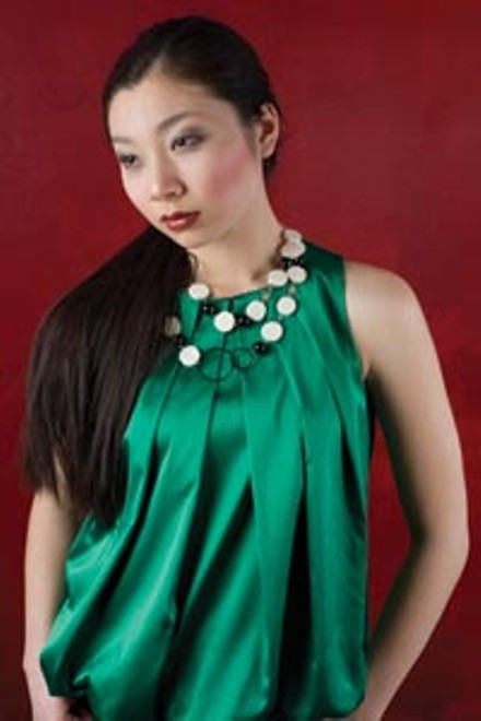 Siran wears: green satin top by Gracia Fashion, available at Jupe Boutique; onyx and African bone necklace by local designer Alma Lleros-Thompson for Alma Jewelry, available at Mia Boutique. - HEATHER MULL