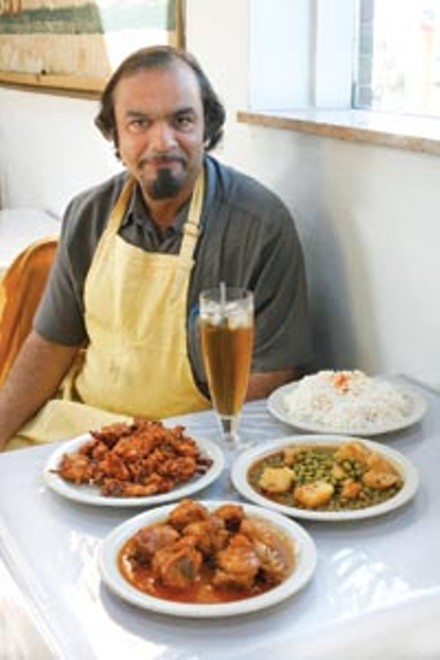 Syed Chand, with traditional Pakistani dishes chicken tikka masala, green peas and potatoes, and vegetable pakora - HEATHER MULL