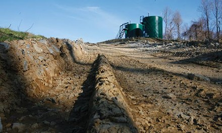 The dirt access road leading to the well pad for two of the natural-gas wells on Ron Gulla's property. The large tanks hold water, petroleum and other byproducts of drilling. - HEATHER MULL
