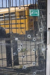 The reflection of an afternoon schoolbus passing by, showin in the bullet-hole riddled door of a vacant bar on the corner of Lincoln Avenue and Rowan Street in District 9 - HEATHER MULL