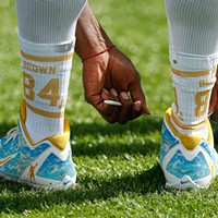 Antonio Brown ties his shoe laces while wearing customized socks during training camp.