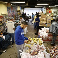 Volunteers stand at their stations while residents pick out food items at the Rainbow Kitchen.
