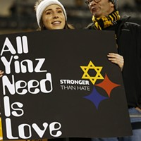 A Pittsburgh Steelers fan holds up a 'All Yinz Need Is Love' sign in honor of the Tree of Life victims.