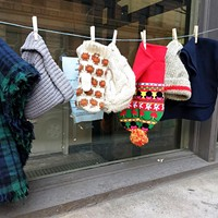 Free hats, gloves, and scarves hang outside the Catholic Charities' Winter Warming Station on Liberty Avenue.