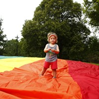 A young pride supporter stands on the gay pride flag at Allegheny Commons Park in the North Side.