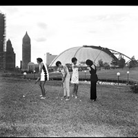 Lynette May, Gerri Walker, Shirley Jenkins, and Alberts Thompson hitting golf balls at Washington Plaza putting field with Civic Arena in the background, 1969