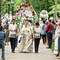 Cerina Wichryk, a member of Oakdale's Filipino community, walks under an archway of flowers.