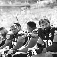 Alejandro Villanueva #78 of the Pittsburgh Steelers sits on the bench in front of the cooling fans.