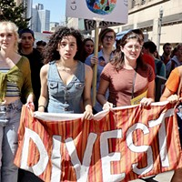 "Sarah Hart, Leandra Mira, Alyssa Martinec, and Hannah Bailey led the protest carrying a sign reading, ""Divest from Fossil Fuels."""