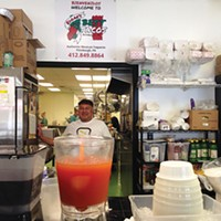 Edgar Alvarez behind the giant jars of <i>aguas frescas</i>