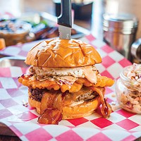 The Yinzer burger with American cheese, bacon, fries, cole slaw, fried egg, hot sauce and mayo