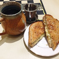 Mug of plum-cinnamon tea and a grilled-cheese sandwich, with brie and pepper jam