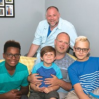 Sean O'Donnell (behind sofa) and his husband Todd Collar (sitting) with their adopted sons A'Sean (left), Elijah (center) and Chris (right) at their home on the North Side