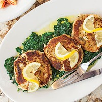 Italian-style crab cakes, served over a bed of sautéed spinach, with a side of pasta