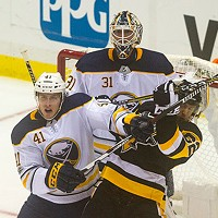 Carl Hagelin battles with Buffalo Sabres Justin Falk in front of the Sabres net.