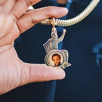 Leon Ford wears a necklace with a picture of his son on one side and a picture of his deceased sister on the other.