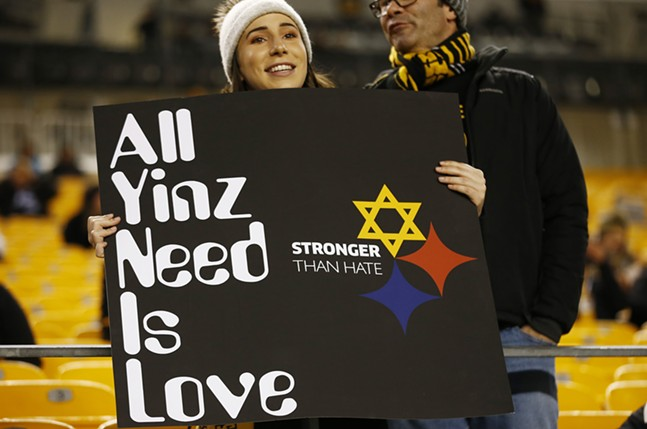 A Pittsburgh Steelers fan holds up a 'All Yinz Need Is Love' sign in honor of the Tree of Life victims. - CP PHOTO: JARED WICKERHAM