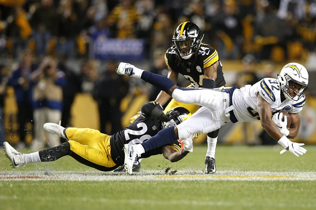 Justin Jackson dives after carrying the ball past Mike Hilton. - CP PHOTO: JARED WICKERHAM