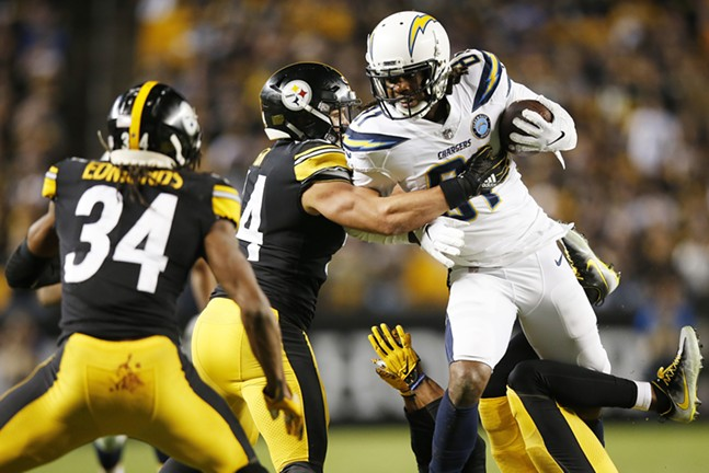 Mike Williams of the Chargers is tackled by L.J. Fort following a catch. - CP PHOTO: JARED WICKERHAM