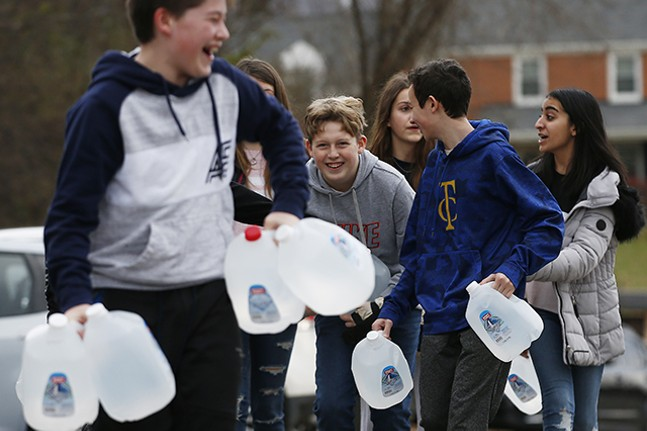 Shadyside Academy eighth grader Parker Mendham, 13, helps his classmates load up water into a car during a 412 Food Rescue - CP PHOTO: JARED WICKERHAM