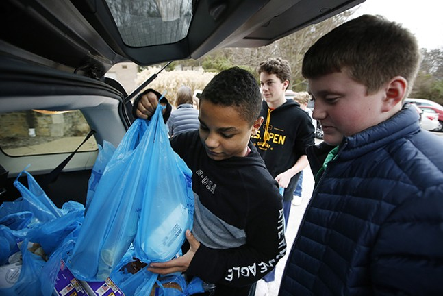 Shadyside Academy eighth grader Maxwell Kimbrough, 13, haps load up food supplies into a car during a 412 Food Rescue - CP PHOTO: JARED WICKERHAM