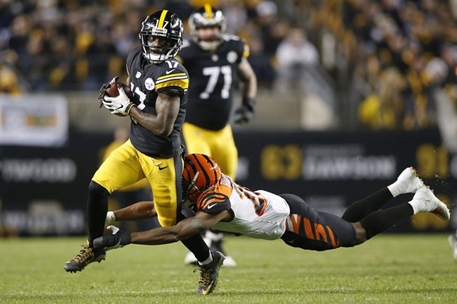 Eli Rogers attempts to escape a tackle after a catch. - CP PHOTO: JARED WICKERHAM