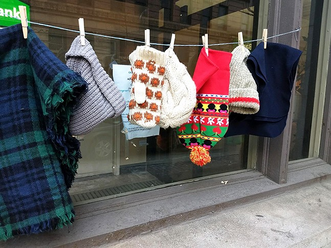 Free hats, gloves, and scarves hang outside the Catholic Charities' Winter Warming Station on Liberty Avenue. - CP PHOTOS: KEVIN SHEPHERD