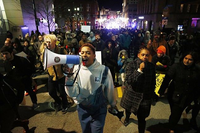 Christian Carter leads the protesters through East Liberty - CP PHOTO: JARED WICKERHAM