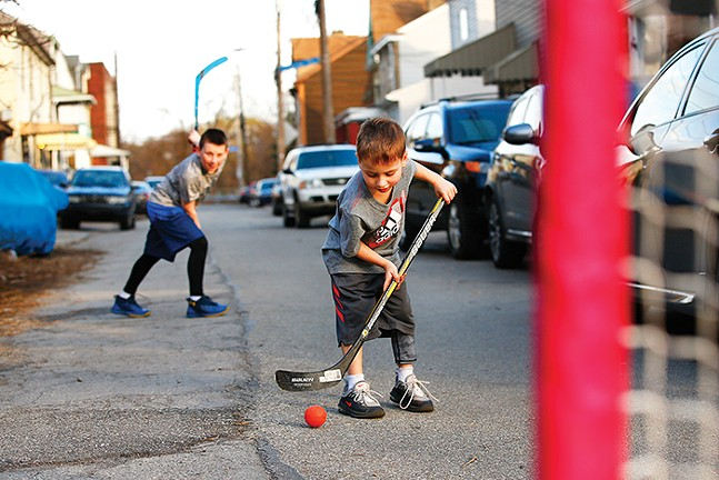 Brady Malcom and Liam Collins play hockey with their dad Chris in Bloomfield. - CP PHOTO: JARED WICKERHAM