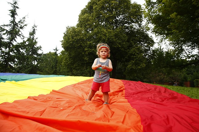 A young pride supporter stands on the gay pride flag at Allegheny Commons Park in the North Side. - CP PHOTO: JARED WICKERHAM