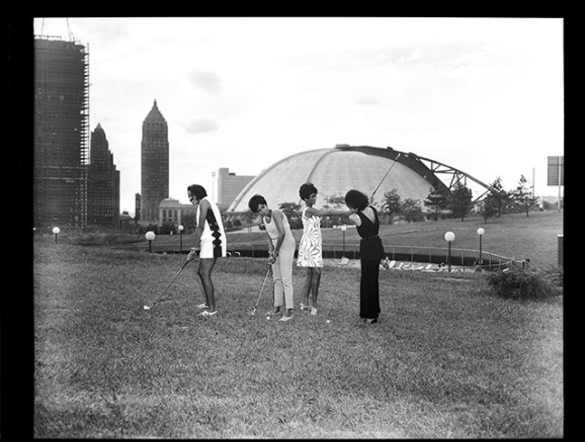 Lynette May, Gerri Walker, Shirley Jenkins, and Alberts Thompson hitting golf balls at Washington Plaza putting field with Civic Arena in the background, 1969 - TEENIE HARRIS