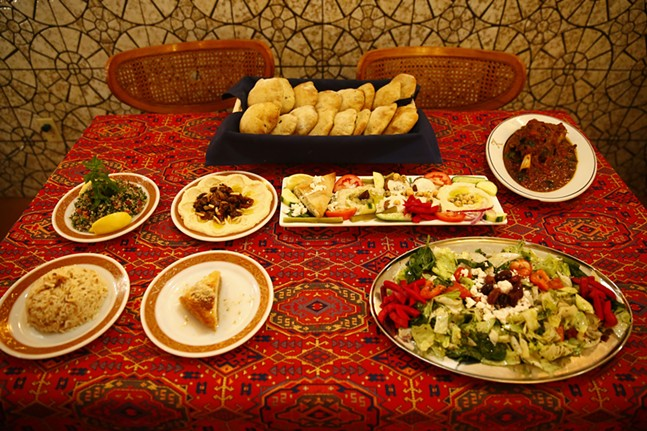 Various dishes including homemade artisan Syrian bread, Tabolli, hummus bi lahme, mazza, mowzat lamb shank, rice, Khalil's signature salad, and desserts - CP PHOTO: JARED WICKERHAM