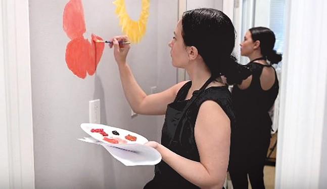 Artist Erin Liposky painting the dressing room at Urbanfitco - URBANFITCO