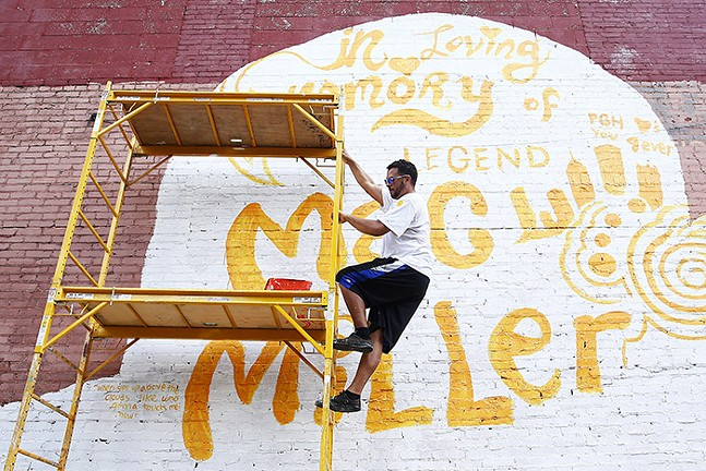 Artist Kyle Holbrook climbs scaffolding before painting the Mac Miller mural in East Liberty - CP PHOTO: JARED WICKERHAM