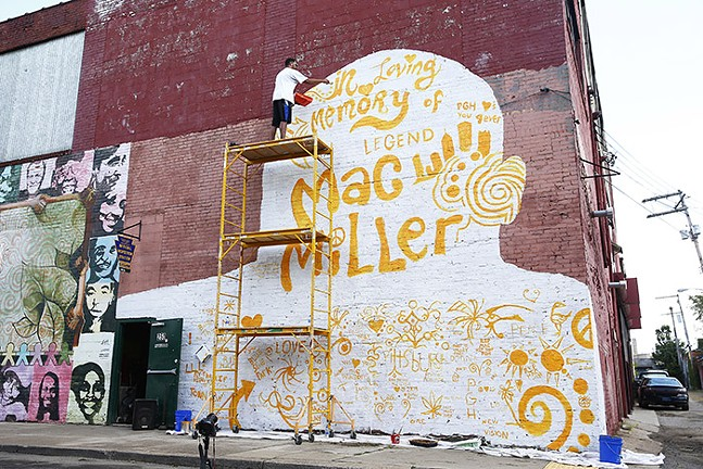 Kyle Holbrook works on the mural. - CP PHOTO: JARED WICKERHAM